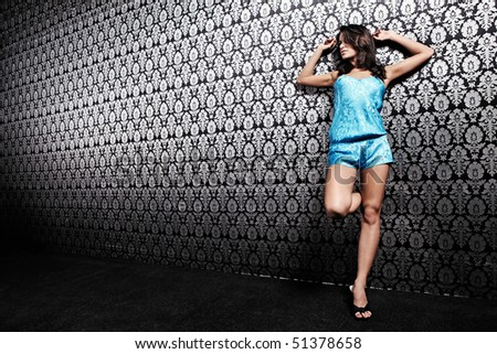 The attractive girl against a wall with an ornament