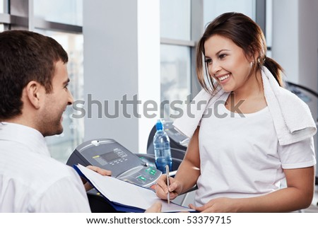 The attractive girl appends the signature in fitness club - stock photo