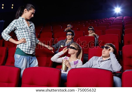 The attractive girl at a cinema makes scandal