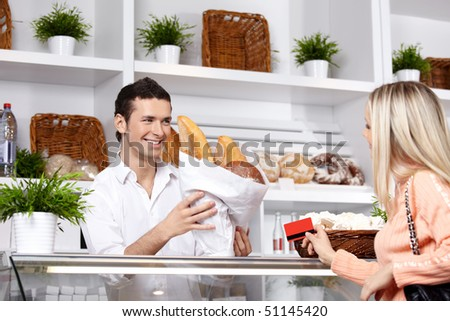 The attractive girl buys bread in shop - stock photo