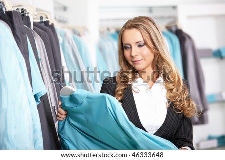 The attractive girl chooses clothes in shop - stock photo