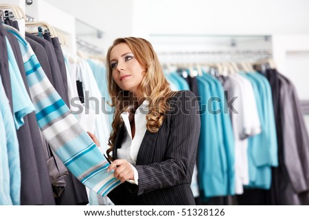 The attractive girl considers clothes in shop - stock photo