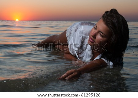 The attractive girl in a white wet transparent dress laying  in sea - stock photo