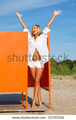 The attractive girl in an orange locker room on a beach - stock photo