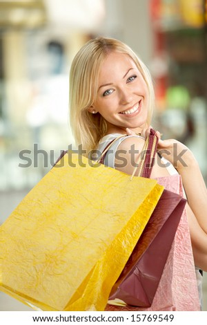 The attractive girl looks and smiles through a shoulder, holding in hands multi-coloured bags with purchases