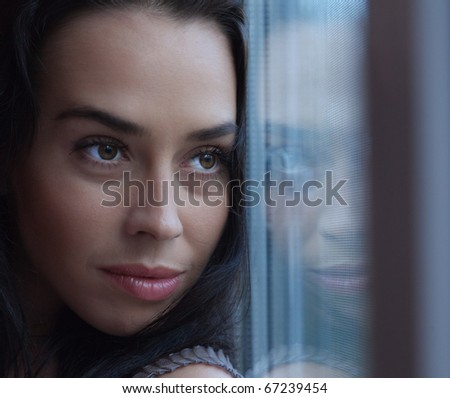 The attractive girl looks out of the window in which her face is reflected