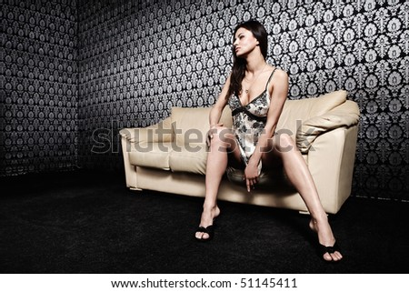 The attractive girl sits on a sofa against a black wall with an ornament - stock photo