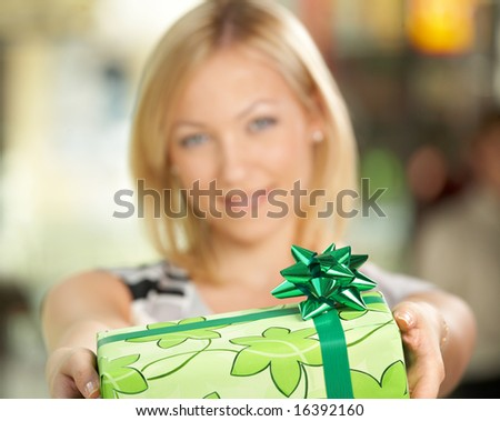 The attractive girl smiles and gives a gift in packing - stock photo