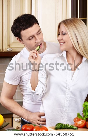 The attractive girl treats the young man on kitchen
