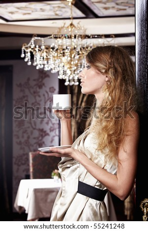 The attractive girl with a white cup on a forward background - stock photo