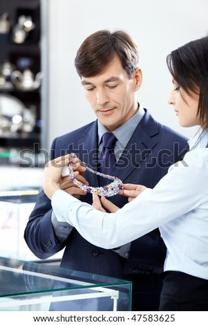 The attractive man chooses a jewel in shop - stock photo