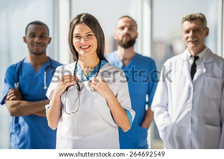 The attractive smiling medical group in hospital. - stock photo