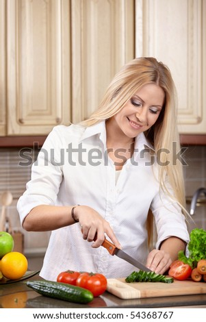 The attractive woman cuts vegetables on kitchen