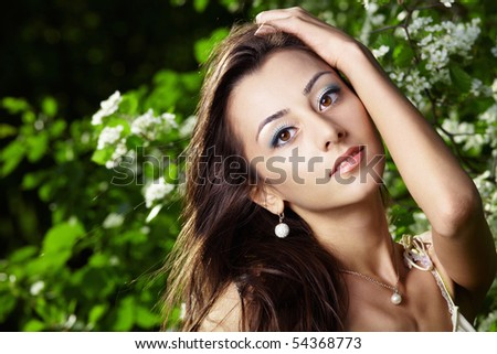 The attractive young girl in greens of trees
