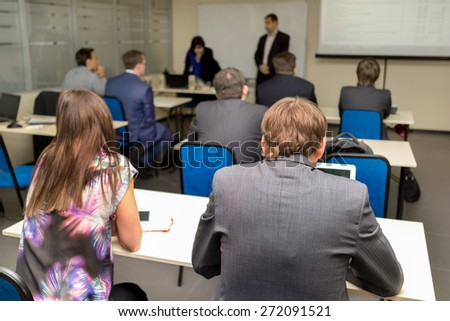 The audience listens to the acting in a classroom