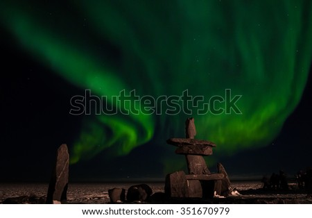 the aurora borealis, behind an inuit structure, with photographers enjoying the northern lights. - stock photo