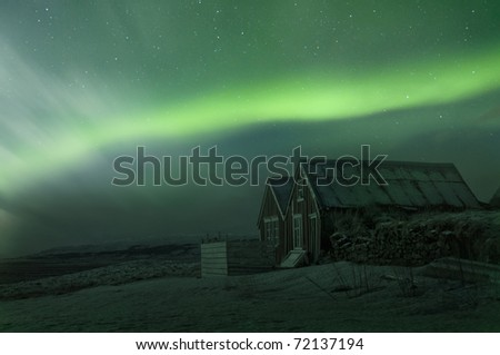 The aurora borealis over a old house in Southern Iceland, Febuary 2011.  grainy image - stock photo