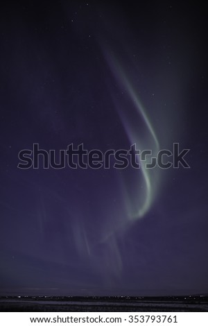 The Aurora Borealis shine over the city lights of Wasilla, Alaska on a cold winter night.