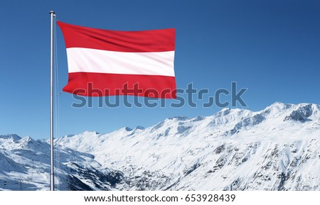 The Austrian flag flying from a metal pole in front of the Oztal Alps in Obergurgl, Austria