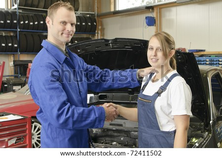 The auto mechanic congratulates its students on passing the exam with flowers in the garage in front of a car - stock photo