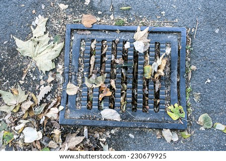 The autumn. Background. manhole, covered with yellow leaves - stock photo