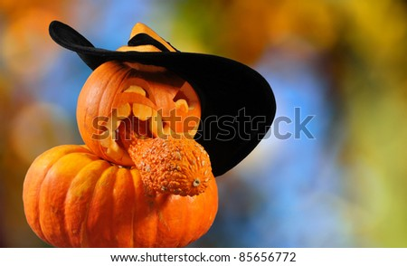 The autumn background with halloween pumpkin in a hat