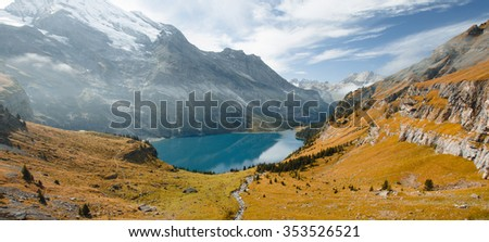 The autumn view over the Oeschinensee mountain lake in Swiss Alps. Panoram