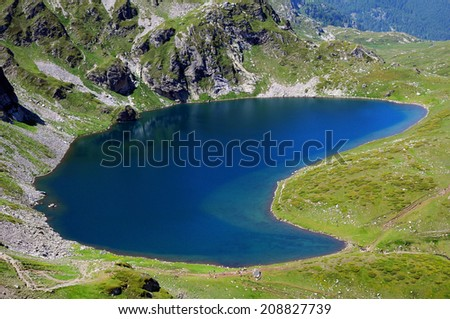 The Babreka (Kidney) glacial lake and its steep cliffy shores in the Rila national park in Bulgaria - stock photo