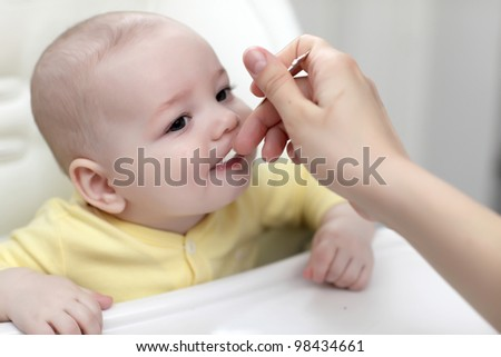 The baby boy eating with spoon at home - stock photo