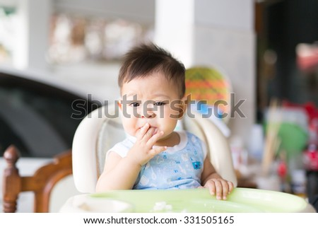the baby boy enjoys eating his food - stock photo