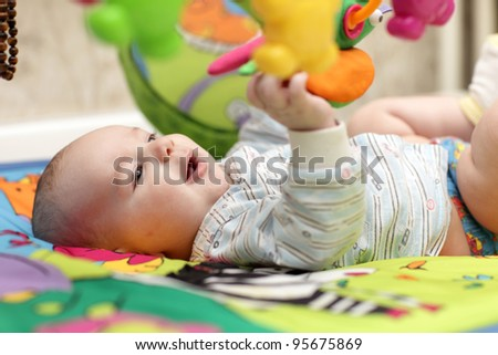 The baby boy playing on a mat at home - stock photo