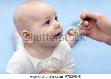 The baby boy taking spoon of iron medicine - stock photo