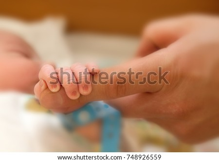 The baby clings to his father's finger