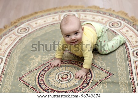 The baby creeping on a carpet at home