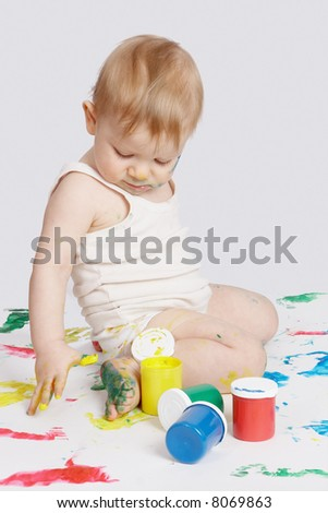 The baby drawing water paints by a finger - stock photo
