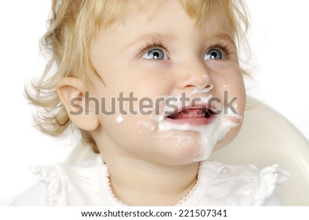 The baby girl eating and smiling with white background - stock photo
