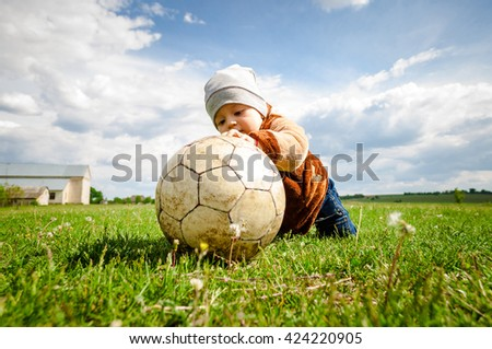 The baby in a cap plays with a ball. - stock photo