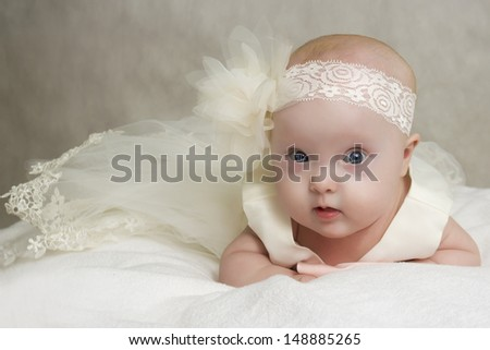 the baby in a dress lies on a pillow