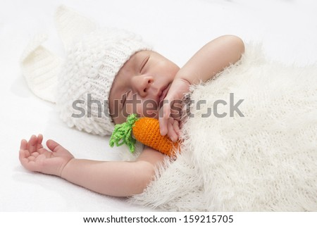 the baby in a suit of a bunny sleeps with carrot