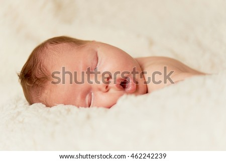 The baby, newly born, lies on the plaid and sleeping, handle the person