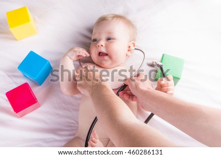 The baby on a white background for inspection at the doctor. Listens stethoscope, smiling, lying around the cubes.