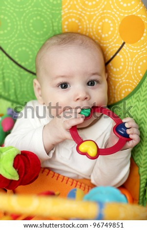 The baby playing with rattle ring at home - stock photo
