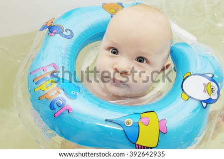 The baby swims in the bathtub