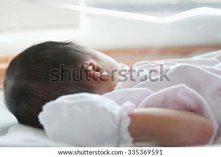 The baby was asleep in a glass case. - stock photo