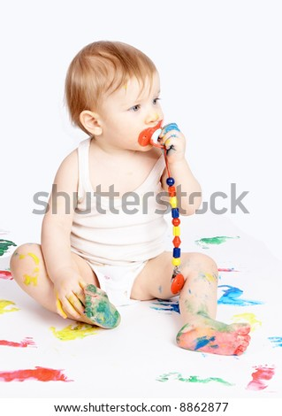 The baby with a dummy sits on a paper - stock photo