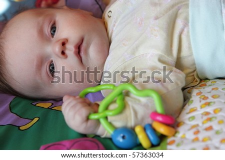 The baby with rattle in bed at home - stock photo