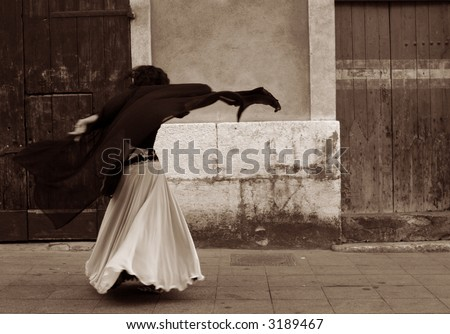 the back of a belly dancer as she dances in the street