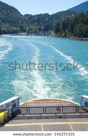 The back of a car ferry leaving a ferry dock in a cove - stock photo