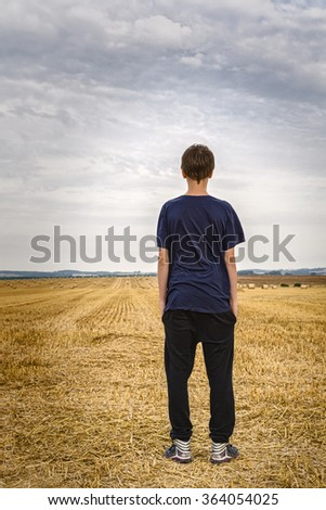the back of a teenage boy looking into the landscape