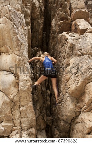 The back of a woman rock climbing up a mountain. - stock photo
